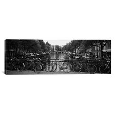 Panoramic Bicycle Leaning against a Metal Railing on a Bridge Canvas